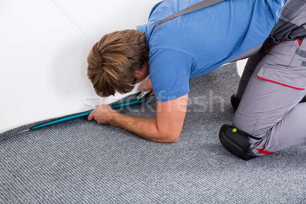 Craftsman Fitting Carpet On Floor Stock photo © AndreyPopov