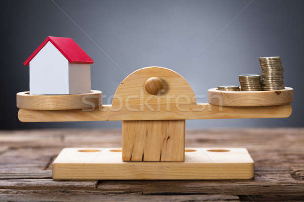 Model Home And Coins Balancing On Wooden Weighing Scale Stock photo © AndreyPopov