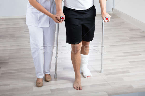 Physiotherapist Helping Injured Man To Walk With Crutches Stock photo © AndreyPopov