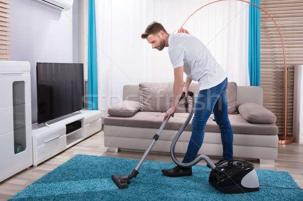 Człowiek czyszczenia dywan odkurzacz młody człowiek niebieski Zdjęcia stock © AndreyPopov