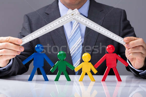 Businessperson Holding Measurement Tape Over Human Figures Stock photo © AndreyPopov