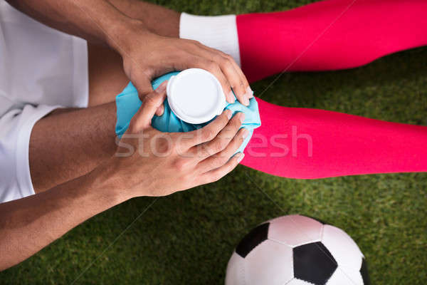 Injured Soccer Player Applying Ice Pack On Knee Stock photo © AndreyPopov