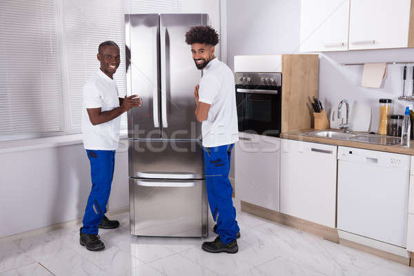 Two Male Movers Fixing The Freezer In The Kitchen Stock photo © AndreyPopov