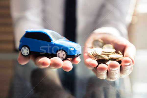 Businessperson Holding Small Blue Car And Golden Coins Stock photo © AndreyPopov