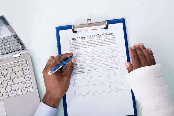 Stock photo: Injured Man Filling Insurance Claim Form