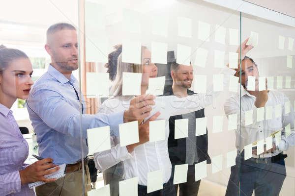 Csoport üzletemberek tapadó jegyzetek üveg fal Stock fotó © AndreyPopov