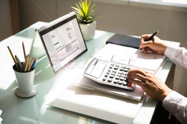 Businessman calculating invoice using calculator Stock photo © AndreyPopov