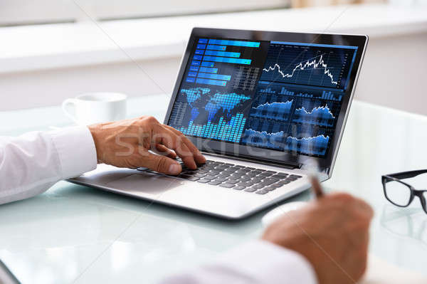 Stock Market Broker Analyzing Graph On Laptop Stock photo © AndreyPopov