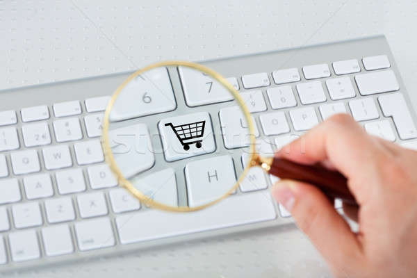Looking at shopping basket key through magnifying glass Stock photo © AndreyPopov