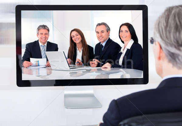 Mature businessman attending video conference Stock photo © AndreyPopov