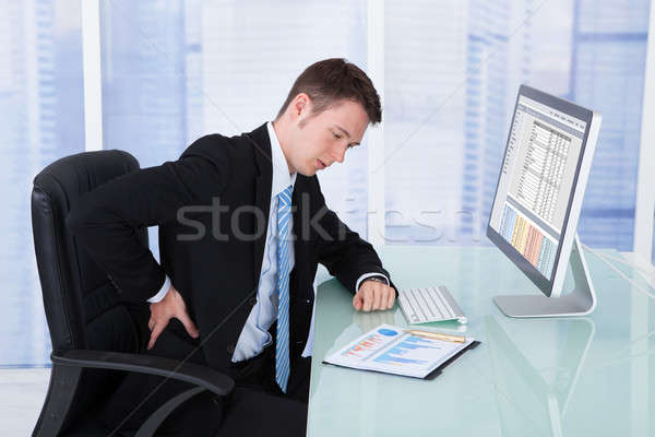 Businessman Suffering From Backache At Computer Desk Stock photo © AndreyPopov