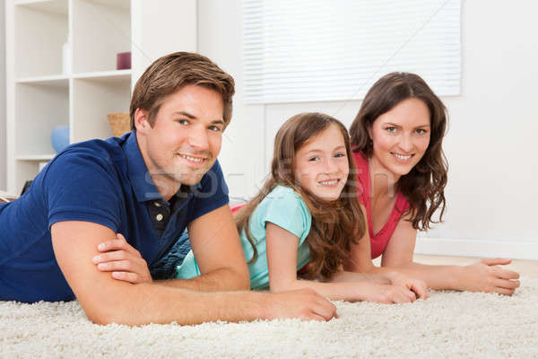 Family Lying Together On Rug At Home Stock photo © AndreyPopov