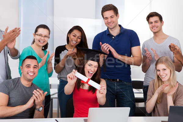 Students Clapping For Classmate Holding Degree Stock photo © AndreyPopov
