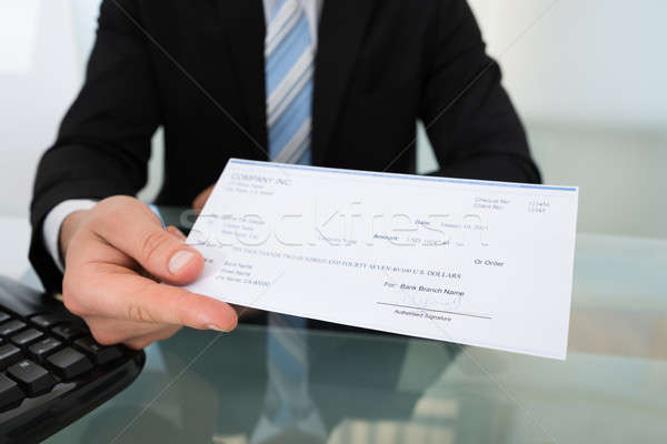 Midsection Of Businessman Giving Cheque Stock photo © AndreyPopov