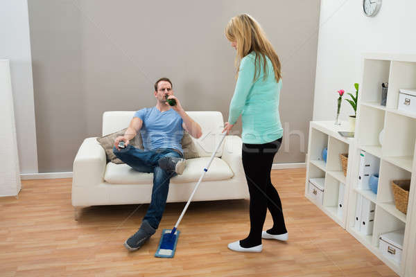Woman Wiping Floor While Man Drinking Alcohol Stock photo © AndreyPopov