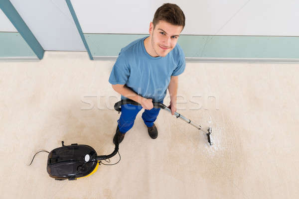 Male Janitor Vacuuming Corridor Stock photo © AndreyPopov