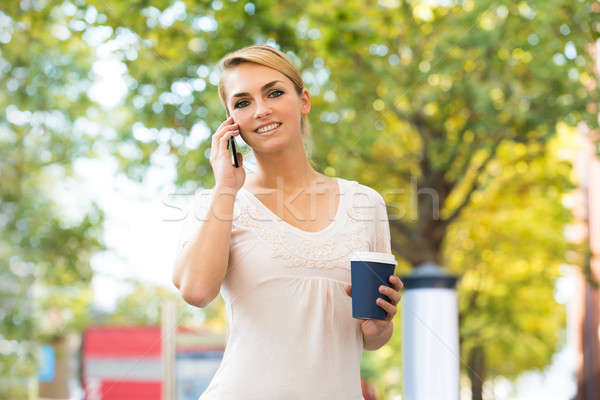 Woman Using Mobile Phone While Holding Disposable Cup Stock photo © AndreyPopov