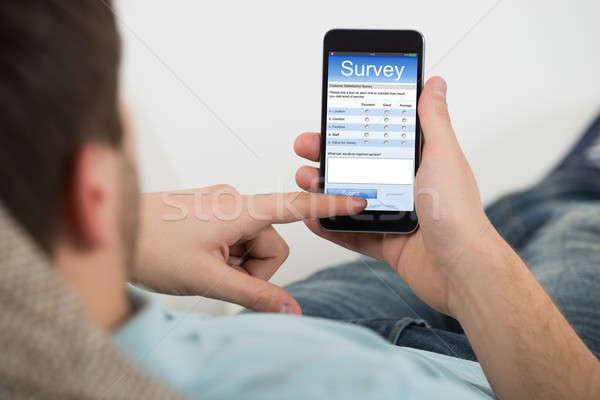 Homme remplissage ligne enquête forme téléphone portable Photo stock © AndreyPopov