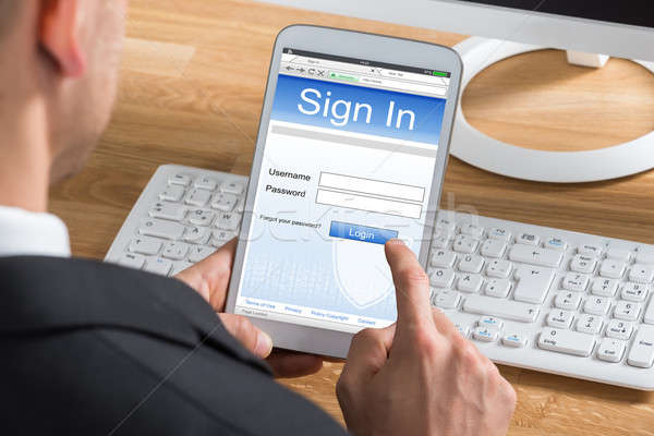 Businessman Signing In Using Digital Tablet Stock photo © AndreyPopov