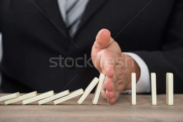 Businessman Hand Stopping Dominoes From Falling On Desk Stock photo © AndreyPopov