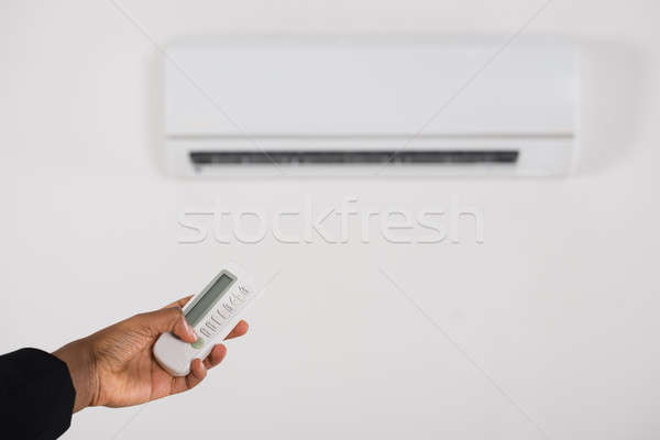 Businesswoman Hand Operating Air Conditioner Stock photo © AndreyPopov