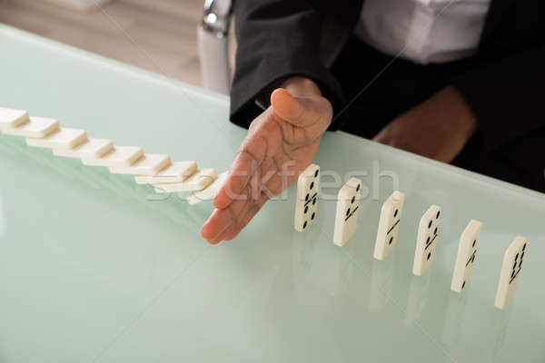Businesswoman Stopping Dominoes From Falling Stock photo © AndreyPopov