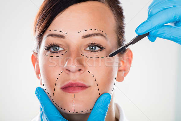 Cosmetic Surgery With Scalpel On Young Woman Stock photo © AndreyPopov