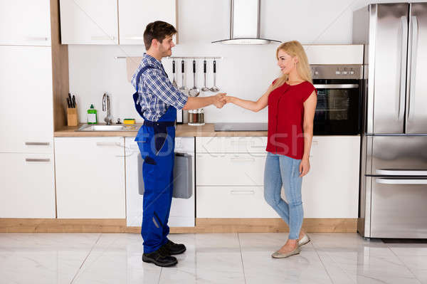 Repairman Shaking Hands With Woman In Kitchen Stock photo © AndreyPopov