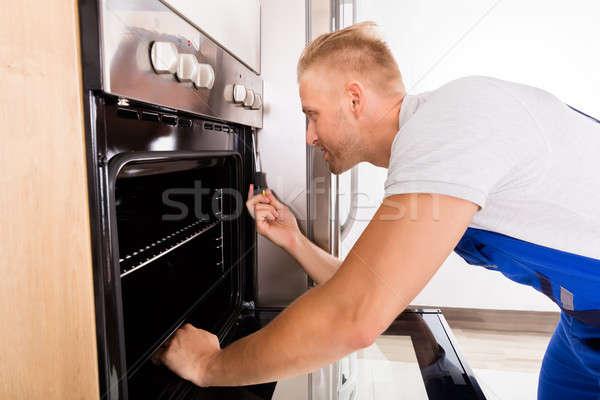 Technik piekarnik młodych mężczyzna kuchnia Zdjęcia stock © AndreyPopov
