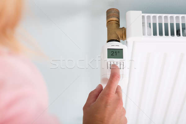 Person Hand Adjusting Temperature On Thermostat Stock photo © AndreyPopov
