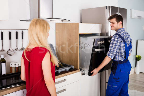 Male Worker Installing Oven For Repairing In Kitchen Stock photo © AndreyPopov