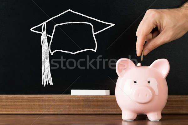 Person Inserting Coin In Piggybank For Completing Education Stock photo © AndreyPopov