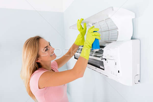 Happy Woman Cleaning The Air Conditioner Stock photo © AndreyPopov