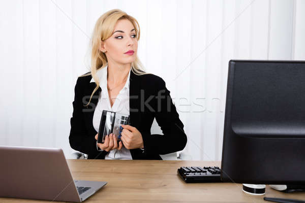Businesswoman Stealing A Calculator Stock photo © AndreyPopov