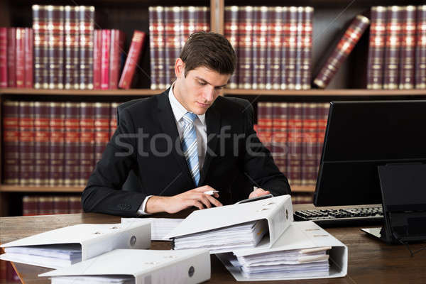 Male Accountant Calculating Invoices On Desk Stock photo © AndreyPopov