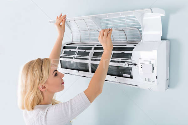 Woman Cleaning Air Conditioning System Stock photo © AndreyPopov