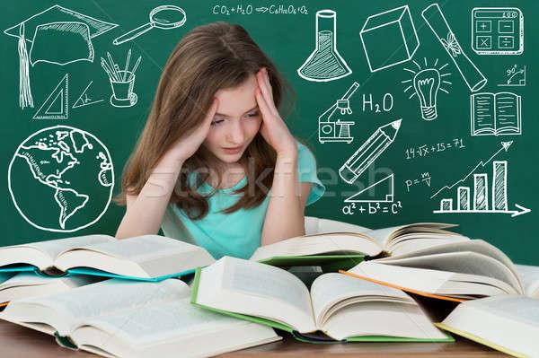 Frustrado menina olhando muitos livros secretária Foto stock © AndreyPopov