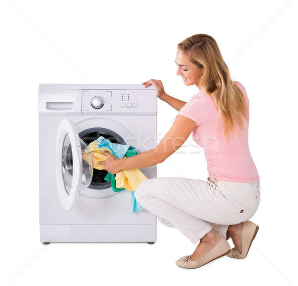 Young Woman Putting Laundry In Washing Machine Stock photo © AndreyPopov