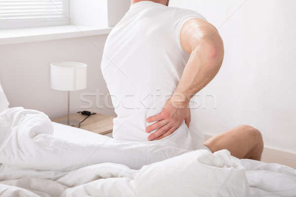 Man Sitting On Bed Having Back Pain Stock photo © AndreyPopov