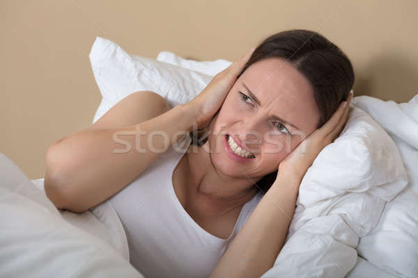 Woman Covering Ears To Shut Out Noise Stock photo © AndreyPopov