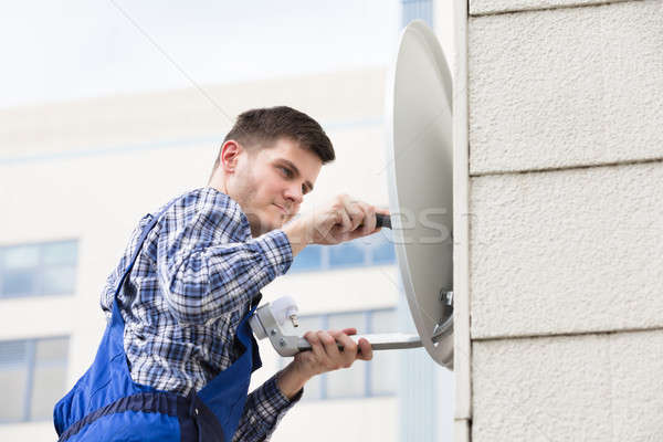 Man Fitting TV Satellite Dish On Wall Stock photo © AndreyPopov