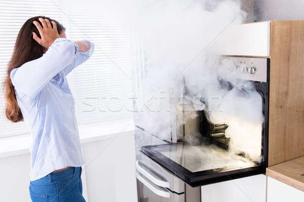 Geschokt vrouw naar rook oven jonge vrouw Stockfoto © AndreyPopov