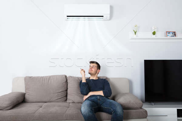 Man Sitting On Couch Operating Air Conditioner Stock photo © AndreyPopov