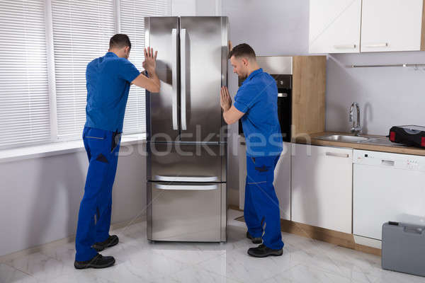 Two Movers Placing Refrigerator In Kitchen Stock photo © AndreyPopov