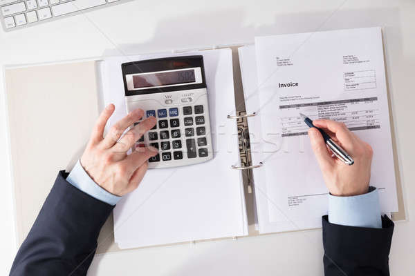 Businessperson Checking Invoice With Calculator Stock photo © AndreyPopov