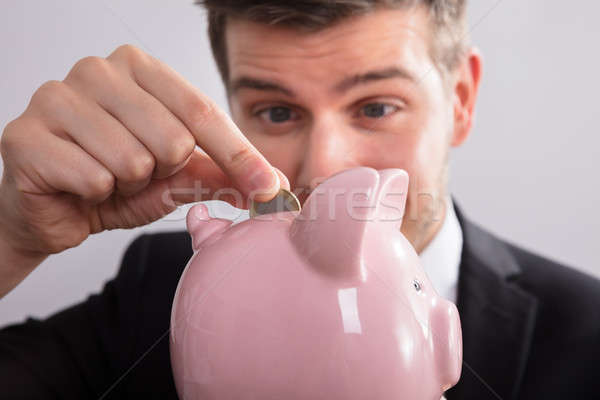 Businessman Inserting Coin In Piggybank Stock photo © AndreyPopov
