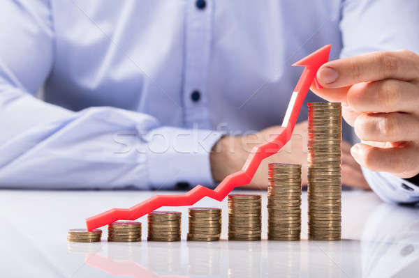 Businessperson Holding Arrow Over Increasing Stacked Coins Stock photo © AndreyPopov