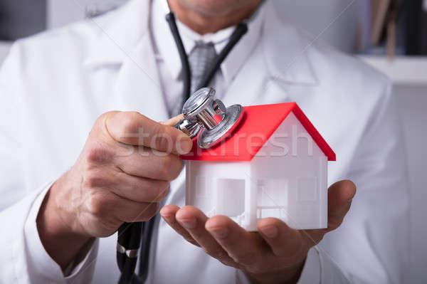 Doctor Holding Stethoscope On House Model Stock photo © AndreyPopov