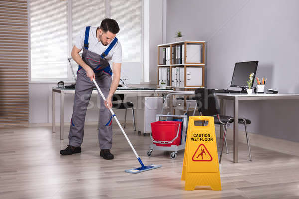 Man Cleaning Hardwood Floor In Office Stock photo © AndreyPopov