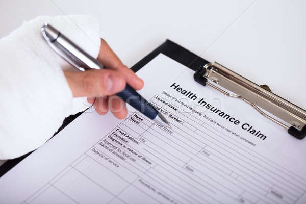 Person With Fractured Hand Filling Medical Benefit Claim Form Stock photo © AndreyPopov
